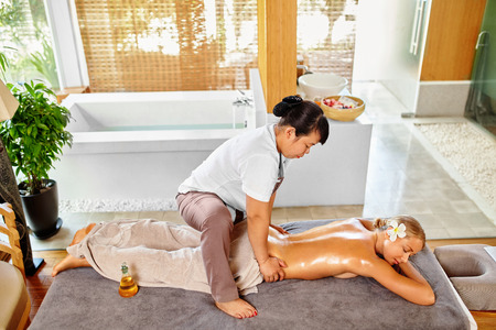 beauty body: Spa Woman. Beauty Treatment. Close-up Of Sexy Healthy Girl Enjoying Relaxing Hand Massage Procedure In Cosmetology Spa Centre, Salon. Masseur Massaging Female Back With Oil. Body, Skin Care Therapy
