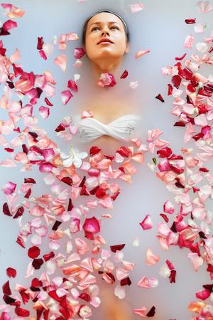 bañarse: Spa Relax En baño de flores. Salud de la mujer y la belleza. Primer hermoso de la muchacha atractiva de baño con pétalos de rosa en Renew Salon Day Spa. Tratamiento de belleza, terapia del cuidado de la piel corporal de aromaterapia. Concepto de la salud