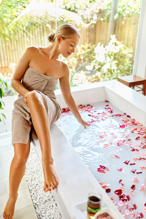 body oil: Woman Spa Body Care Treatment. Beautiful Sexy Blonde Girl In Towel Sitting Near Flower Rose Bath In Day Spa Salon. Beauty Therapy, Relaxing Procedure. Skin Care, Wellness, Healthy Lifestyle Concept