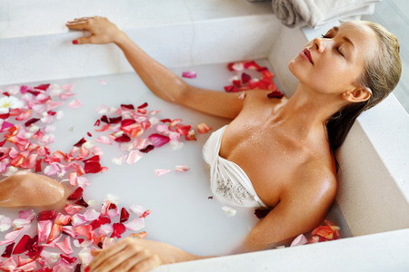 sexy bath: Woman In Spa Flower Bath. Aromatherapy. Closeup Portrait Of Beautiful Sexy Young Female Relaxing In Rose Bath Tub In Resort Day Spa Salon. Beauty Treatment. Skin Body Care. Healthy Lifestyle Concept