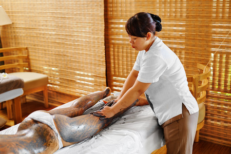 clays: Body Care. Spa Treatment. Beautiful Sexy Young Woman Receiving Cosmetic Clay, Marine Algae Body Mask Lying On Massage Table At Beauty Salon. Skin Care Wrap Therapy. Healthy Lifestyle, Wellness Concept
