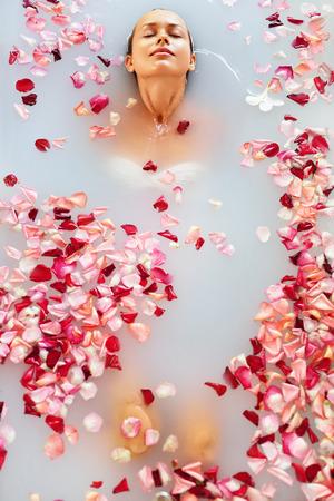 スパは、フラワー ・ バスでリラックスします。女性の健康と美容。クローズ アップ美しいセクシーな女の子でバラの花びらで入浴は更新日スパ サ