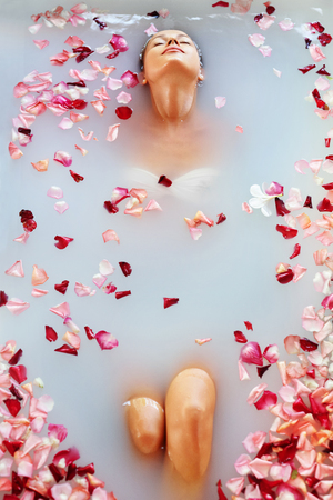 bath girl: Spa Relax In Flower Bath. Woman Health And Beauty. Closeup Beautiful Sexy Girl Bathing With Rose Petals In Renew Day Spa Salon. Beauty Treatment, Aromatherapy Skin Body Care Therapy. Wellness Concept Stock Photo