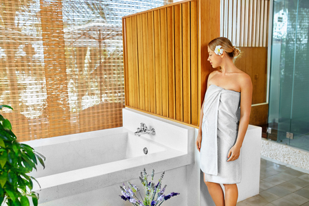 day spa: Woman Spa Body Care Treatment. Beautiful Sexy Blonde Female In Towel Going To Take Flower Bath In Renew Day Spa Salon. Beauty Therapy, Relaxing Procedure. Skincare, Wellness, Healthy Lifestyle Concept Stock Photo