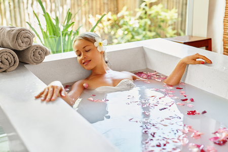 health woman: Health And Beauty. Woman Spa Body Care Procedure. Closeup Attractive Sexy Blonde Female In Bikini Relaxing In Flower Rose Bath In Day Spa Centre. Beauty Treatment, Skincare Therapy Concept. Wellness