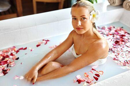 mujer con rosas: Tratamiento Cuidado del cuerpo Belleza Spa. Retrato de detalle de hermosa sonriente de la muchacha modelo de relax en la flor de la tina de baño en el salón. Cuidado de la piel, de limpieza Procedimiento Concepto. Estilo de vida saludable, bienestar Foto de archivo