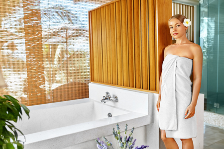 sexy bath: Woman Spa Body Care Treatment. Beautiful Sexy Blonde Female In Towel Going To Take Flower Bath In Renew Day Spa Salon. Beauty Therapy, Relaxing Procedure. Skincare, Wellness, Healthy Lifestyle Concept Stock Photo