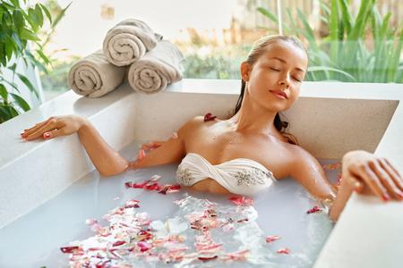 mujer bañandose: Spa Relax En baño de flores. Salud de la mujer y la belleza. Primer hermoso de la muchacha atractiva de baño con pétalos de rosa en Renew Salon Day Spa. Tratamiento de belleza, terapia del cuidado de la piel corporal de aromaterapia. Concepto de la salud