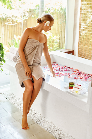bath: Woman Spa Body Care Treatment. Beautiful Sexy Blonde Girl In Towel Sitting Near Flower Rose Bath In Day Spa Salon. Beauty Therapy, Relaxing Procedure. Skin Care, Wellness, Healthy Lifestyle Concept