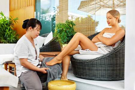 recreational: Spa Foot Therapy. Woman Body Care Treatment. Masseur Massaging Young Female Feet With Aromatherapy Oil Outside In Spa Salon Garden. Relaxing Recreational Massage. Skin Care, Beauty Procedure Concept