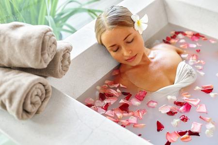 personas banandose: Spa Relax En baño de flores. Salud de la mujer y la belleza. Primer hermoso de la muchacha atractiva de baño con pétalos de rosa en Renew Salon Day Spa. Tratamiento de belleza, terapia del cuidado de la piel corporal de aromaterapia. Concepto de la salud