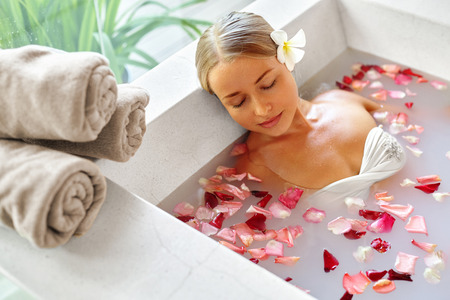 Spa Relax In Flower Bath. Woman Health And Beauty. Closeup Beautiful Sexy Girl Bathing With Rose Petals In Renew Day Spa Salon. Beauty Treatment, Aromatherapy Skin Body Care Therapy. Wellness Concept Stock Photo