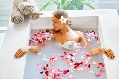 bath girl: Health And Beauty. Woman Spa Body Care Procedure. Closeup Attractive Sexy Blonde Female In Bikini Relaxing In Flower Rose Bath In Day Spa Centre. Beauty Treatment, Skincare Therapy Concept. Wellness