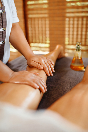 Body Care. Spa Massage Therapy. Closeup Masseur Massaging Long Female Legs With Essential Oil In Cosmetology Salon. Healthy Woman Getting Body Contouring, Anti-cellulite Procedure. Skin Care Treatment