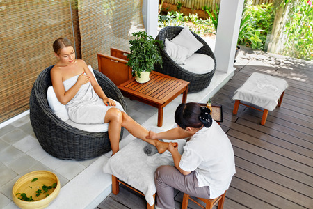 Leg Massage Therapy In Spa Salon. Body, Skin Care. Beautiful Young Woman Relaxing, Masseur Massaging Long Female Legs With Aromatherapy Oil. Beauty Treatment Concept. Wellness, Healthy Lifestyle.