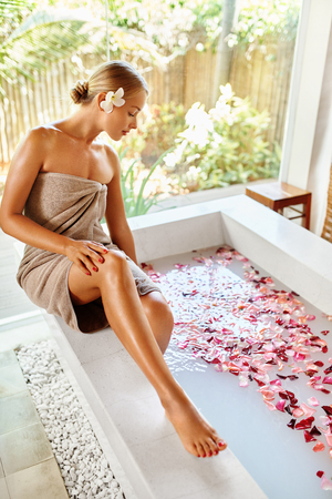 spa woman: Woman Spa Body Care Treatment. Beautiful Sexy Blonde Girl In Towel Sitting Near Flower Rose Bath In Day Spa Salon. Beauty Therapy, Relaxing Procedure. Skin Care, Wellness, Healthy Lifestyle Concept