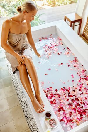 sexy bath: Skin Care Spa Treatment. Sexy Young Woman In Towel Sitting On Bathtub, Preparing Aromatherapy Flower Rose Bath In Resort Day Spa Centre. Beauty Therapy. Bodycare, Wellness, Healthy Lifestyle Concept