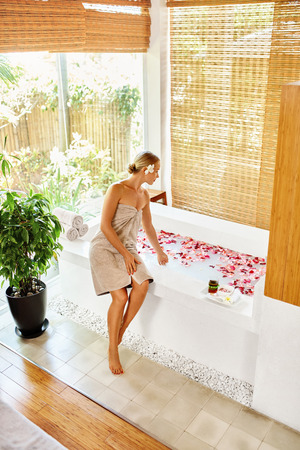 beauty body: Woman Spa Body Care Treatment. Beautiful Sexy Blonde Girl In Towel Sitting Near Flower Rose Bath In Day Spa Salon. Beauty Therapy, Relaxing Procedure. Skin Care, Wellness, Healthy Lifestyle Concept