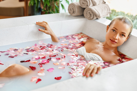young girl bath: Woman In Spa Flower Bath. Aromatherapy. Closeup Portrait Of Beautiful Sexy Young Female Relaxing In Rose Bath Tub In Resort Day Spa Salon. Beauty Treatment. Skin Body Care. Healthy Lifestyle Concept