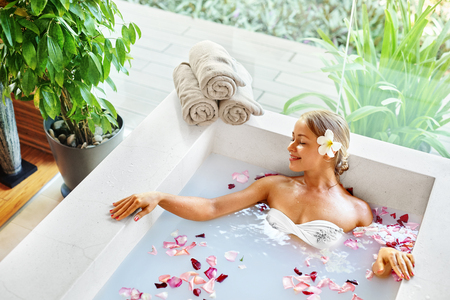 bath: Spa Relax In Flower Bath. Woman Health And Beauty. Closeup Beautiful Sexy Girl Bathing With Rose Petals In Renew Day Spa Salon. Beauty Treatment, Aromatherapy Skin Body Care Therapy. Wellness Concept Stock Photo