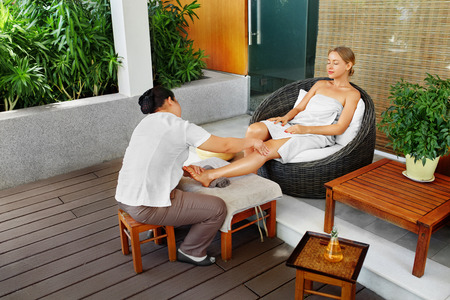 recreational: Spa Woman Body Care. Aromatherapy Oil Leg Massage. Masseur Massaging Girl Long Legs Outside In Beauty Salon Garden Terrace. Relaxing Recreational Skincare Treatment, Therapy Concept. Healthy Lifestyle