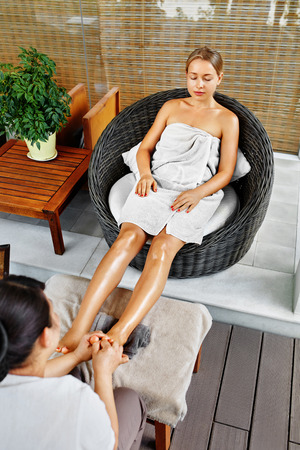 massager: Spa Body Care. Foot Massage. Beautiful Young Woman Relaxing While Masseur Massaging Feet With Aromatherapy Oil In Spa Salon. Beauty Treatment, Therapy Concept. Skin Care, Wellness, Healthy Lifestyle