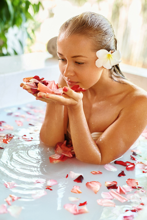 Woman Body Care. Spa Bath With Rose Petals. Close-up Of Sexy Blonde Female In Bikini Taking Flower Bath In Resort Day Spa Centre. Beauty Treatment, Aroma Therapy. Skin Care. Healthy Lifestyle Concept
