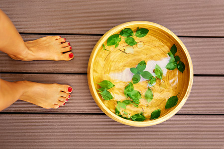 Body Care. Female Feet At Spa Pedicure Procedure. Foot Bath Basin, Bowl With Water, Peppermint, Ginger, Essential Oils For Relaxing  Aromatherapy Treatment In Salon. Skin Therapy, Healthy Lifestyle