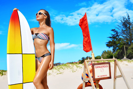summertime: Summer Adventure. Water Sports. Surfing. Sexy Sporty Surfer Girl With Fit Body In Bikini With Surfboard Enjoying Holidays Travel Vacation On Beach. Healthy Active Lifestyle. Leisure Sport. Summertime