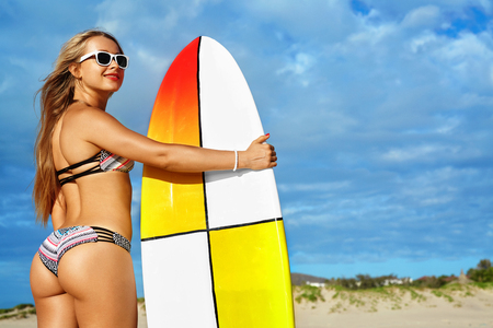 water sports: Fitness Girl. Extreme Summer Water Sports. Surfing. Healthy Fit Woman With Perfect Sexy Body And Butt, Buttocks In Bikini Posing With Surfboard On Ocean Beach. Vacations, Lifestyle, Beauty, Health Stock Photo