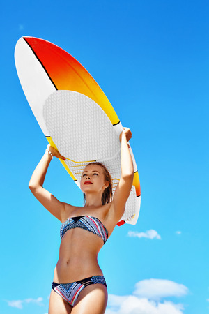 recreational sports: Recreational Summer Water Sports. Surfing. Beautiful Smiling Young Surfer Woman In Bikini With Surfboard At Beach On Holidays Vacation. Healthy Lifestyle. Leisure Activity. Summertime Hobby, Enjoyment