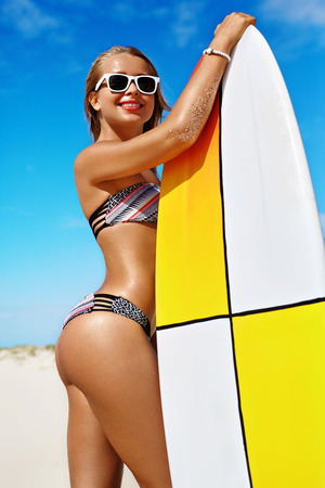 surfboard: Sports. Surfing. Healthy Active Lifestyle. Summer Vacations. Athletic Surfer Woman, Girl With Sexy Body In Bikini With Surfboard Sunbathing On Sea Beach. Extreme Water Sport. Summertime Relaxation.