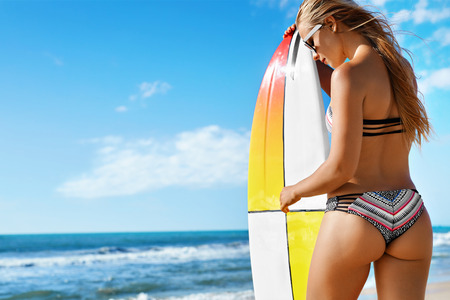 fit: Fitness Girl. Extreme Summer Water Sports. Surfing. Healthy Fit Woman With Perfect Sexy Body And Butt, Buttocks In Bikini Posing With Surfboard On Ocean Beach. Vacations, Lifestyle, Beauty, Health Stock Photo