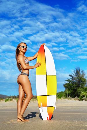 Sommer Wassersport. Strand-Ferien. Surfen. Schöne Fit Smiling Surfer Frau mit sexy Körper posiert im Bikini mit Surfbrett am Strand. Gesunde aktiven Lebensstil. Freizeit Sport. Hobby, Wellness