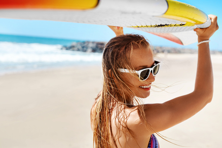 summer holiday: Summer Fun On Holidays Travel Vacation. Surfing. Sexy Beautiful Surfer Girl In Bikini With Surfboard. Healthy Lifestyle. Extreme Water Sports. Summertime Leisure Activity. Hobby. Wellness Concept Stock Photo