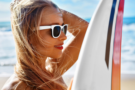 sporting activity: Summer Travel Beach Vacation. Close Up Of Healthy Happy Beautiful Sexy Woman In Sunglasses With Surfboard Having Fun By Sea. Active Lifestyle. Leisure Sporting Activity. Water Sports. Summertime Relax