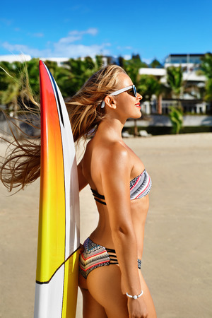 surf: Sports. Surfing. Healthy Active Lifestyle. Summer Vacations. Athletic Surfer Woman, Girl With Sexy Body In Bikini With Surfboard Sunbathing On Sea Beach. Extreme Water Sport. Summertime Relaxation.