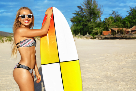 extreme sports: Summer Fun. Leisure Sporting Activity. Surfing. Healthy Beautiful Smiling Surfer Woman In Bikini And Sunglasses With Surfboard On Ocean Beach. Extreme Water Sports. Holidays Vacation. Lifestyle. Hobby Stock Photo