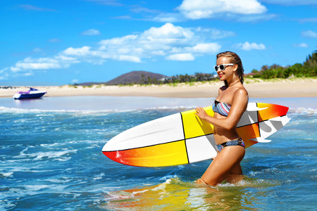 Summer Fun. Happy Young Surfer Woman With Sexy Fit Body In Fashion Bikini With Surfing, Surf Board In Sea Water Enjoying Travel Vacation To Tropical Resort. Sports, Healthy Lifestyle, Wellness.