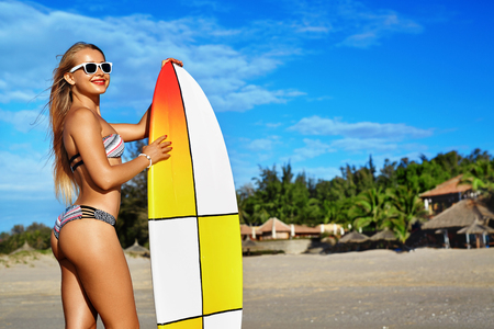 sporting activity: Summer Fun. Leisure Sporting Activity. Surfing. Healthy Beautiful Smiling Surfer Woman In Bikini And Sunglasses With Surfboard On Ocean Beach. Extreme Water Sports. Holidays Vacation. Lifestyle. Hobby Stock Photo