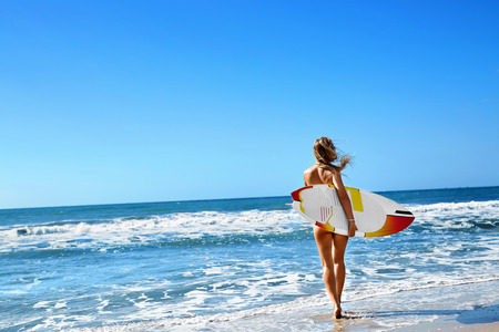 Healthy Active Lifestyle. Surfing. Water Sports. Beautiful Athletic Surfer Woman With Sexy Fit Body In Bikini With Surf Board Walking On Sea Beach. Summer Vacation. Extreme Sport. Summertime Fun Hobby Stock Photo