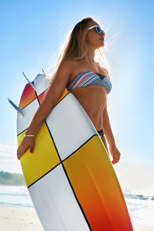 recreational sports: Recreational Water Sports In Summer. Surfing. Beautiful Athletic Smiling Girl With Sexy Body In Bikini Having Fun, Holding Surfboard On Sea Beach. Holidays Vacation. Healthy Lifestyle. Sport. Hobby