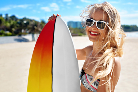Summer Travel Beach Vacation. Close Up Of Healthy Happy Beautiful Sexy Woman In Sunglasses With Surfboard Having Fun By Sea. Active Lifestyle. Leisure Sporting Activity. Water Sports. Summertime Relax
