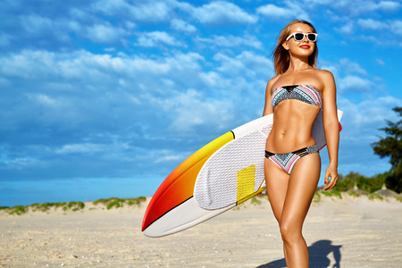 sporting activity: Water Sports. Surfing. Healthy Happy Sexy Fit Surfer Woman, Girl In Bikini Having Fun With Surfboard On Sea Beach. Summer Holidays Vacation. Lifestyle. Leisure Sporting Activity. Summertime Relaxation