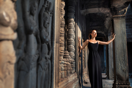 buddhist's: Cambodia Tourist Attraction. Happy Beautiful Religious Young Woman Relaxing In Corridor At Prasat Angkor Khmer Wat Temple, Siem Reap. Famous Landmark, Travel Destination. Harmony, Tranquility Concept