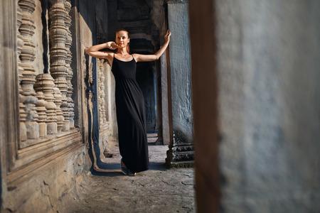 armonia: Camboya atracción turística. Mujer feliz hermosa joven religiosa que se relaja en Corredor en Prasat Angkor Khmer templo Wat, Siem Reap. Señal famosa, Destino del viaje. Armonía, Tranquilidad