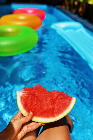 female hands: Summer Vacation. Summertime Fun. Female Hand Holding Slice Of Ripe Juicy Watermelon By The Swimming Pool. Colorful Floating Rings In Refreshing Blue Water On Background. Freshness, Enjoyment Concept