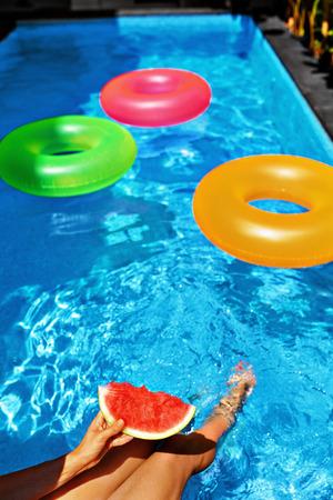 frescura: Vacaciones de verano. Diversión del verano. Mano femenina que sostiene rebanada de sandía jugosa madura en la piscina. Anillos flotantes coloridos en Refrescante agua azul en el fondo. Frescura, Placer