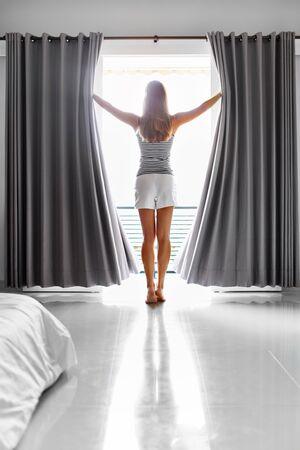 Morning. Beautiful Sexy Young Woman With Fit Slim Body Opening Curtains In Bedroom. Girl Standing Near Window At Home. New Day Concept. Wellness, Healthy Lifestyle.