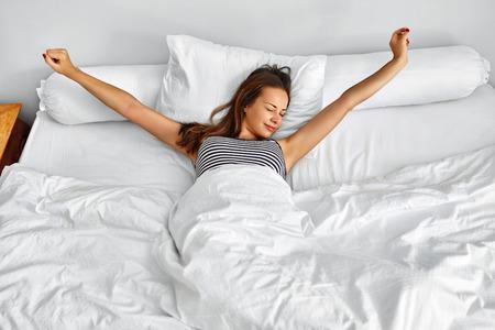 Manhã Acorde. Jovem mulher de sorriso que acorda descansada inteiramente no fundamento branco. Esticão modelo na cama. Menina Deitada, Relaxando No Quarto. Sono saudável, estilo de vida. Bem-Estar, Saúde, Conceito de Beleza